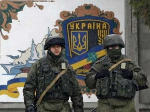Uniformed troops believed to be Russian stand guard outside a Ukrainian military base in Crimea. Is there a peaceful resolution to this crisis? [Credit: Business Insider]